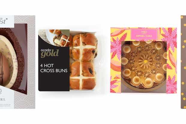 Une rangée d'oeufs de Pâques, de petits pains croisés chauds et de gâteaux simnel