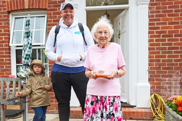 Tom Kerridge and an older lady outside a redbrick building