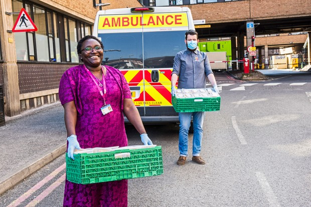 A man and a woman holding crates outside an ambulance