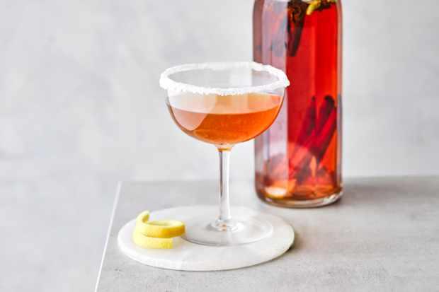 Cocktail de Sidecar dans un verre coupé avec une bouteille de liquide rouge derrière