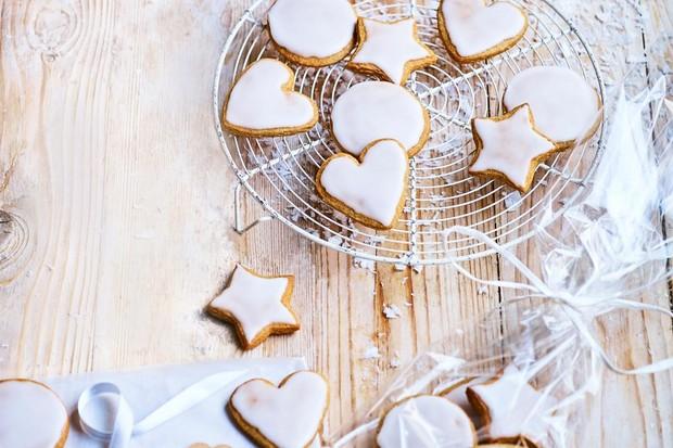 Une assiette de biscuits en forme avec un glaçage blanc sur le dessus, posée sur une grille