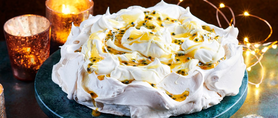 A whole pavlova on a blue serving platter, with passion fruit drizzle on top and fairy lights in the background