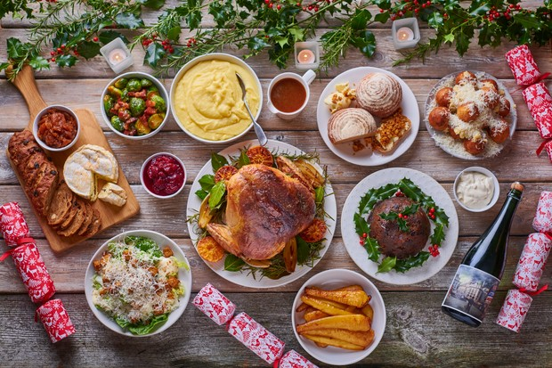 A wooden table lined with a Christmas feast – turkey, carrots, bread sauce, bread, sprouts, crackers and holly