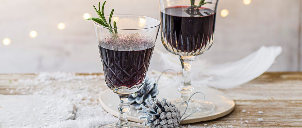 Two glasses of mulled port with sprig of rosemary inside