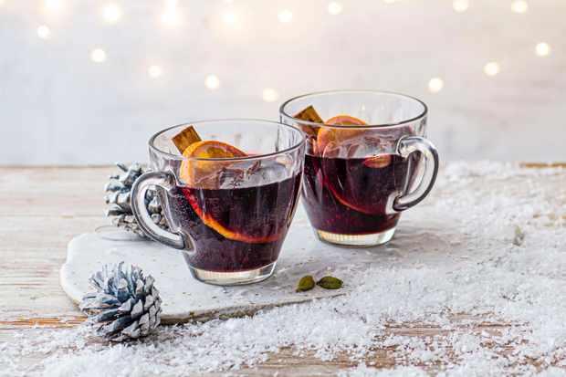 Deux tasses en verre remplies de vin rouge chaud avec une tranche d'orange dans chacune