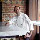 Jose Pizarro in chef whites with a glass of sherry in hand