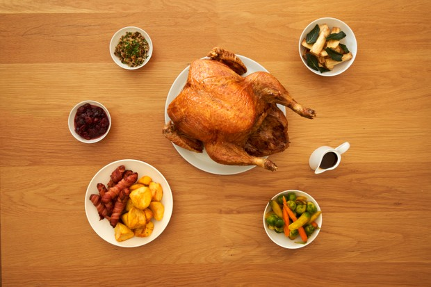 A wooden table with a turkey, pigs in blankets, gravy boat, potatoes, veg from a bird's eye view