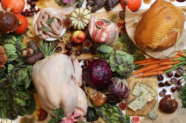 A table piled with Christmas produce including raw turkey, uncooked sausages, fresh red cabbage, fruit, gourds and more