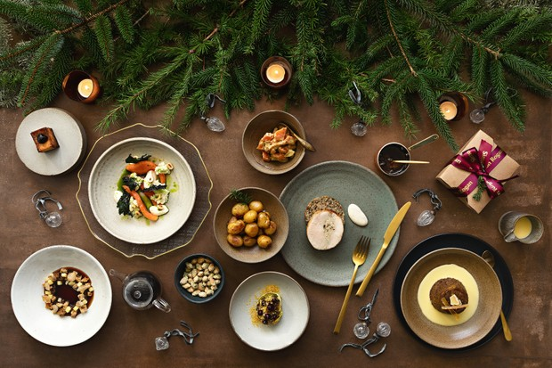 A table lined with turkey crown, roast potatoes and small ceramic plates of Christmas food