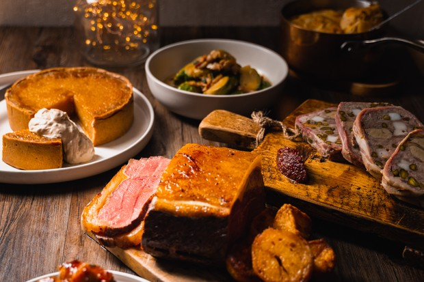 A table set with a pumpkin pie, beef joint, pistachio-stuffed terrine and a bowl of sprouts
