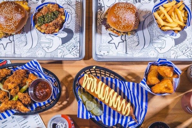Libertine Burgers on trays with a hot dog on the side