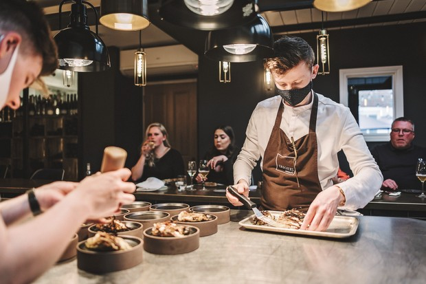 Two chefs plating dishes at a chefs table