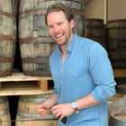 Ronan Collins in a blue shirt in front of whisky barrels