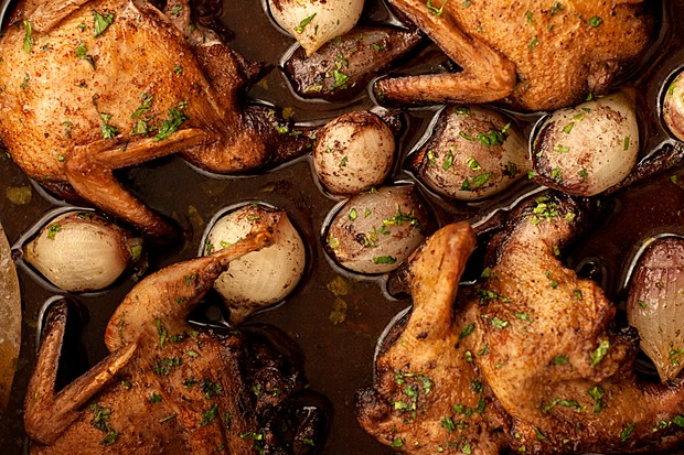 A close up of a quail casserole with small white onions and green herbs