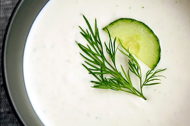 A close up of a bowl of white soup topped with a slice of green cucumber and sprig of dill