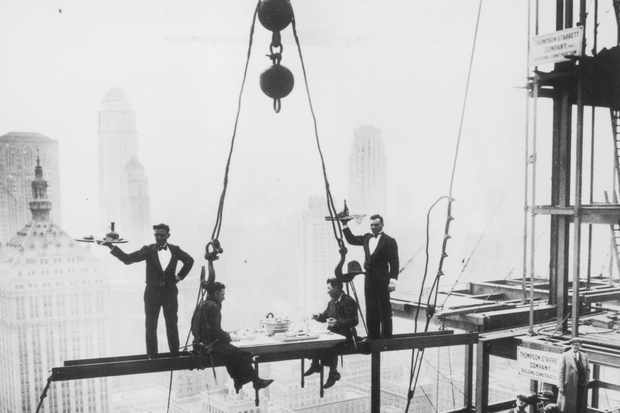 Two waiters serve two steel workers lunch, on a girder high above New York City © Getty