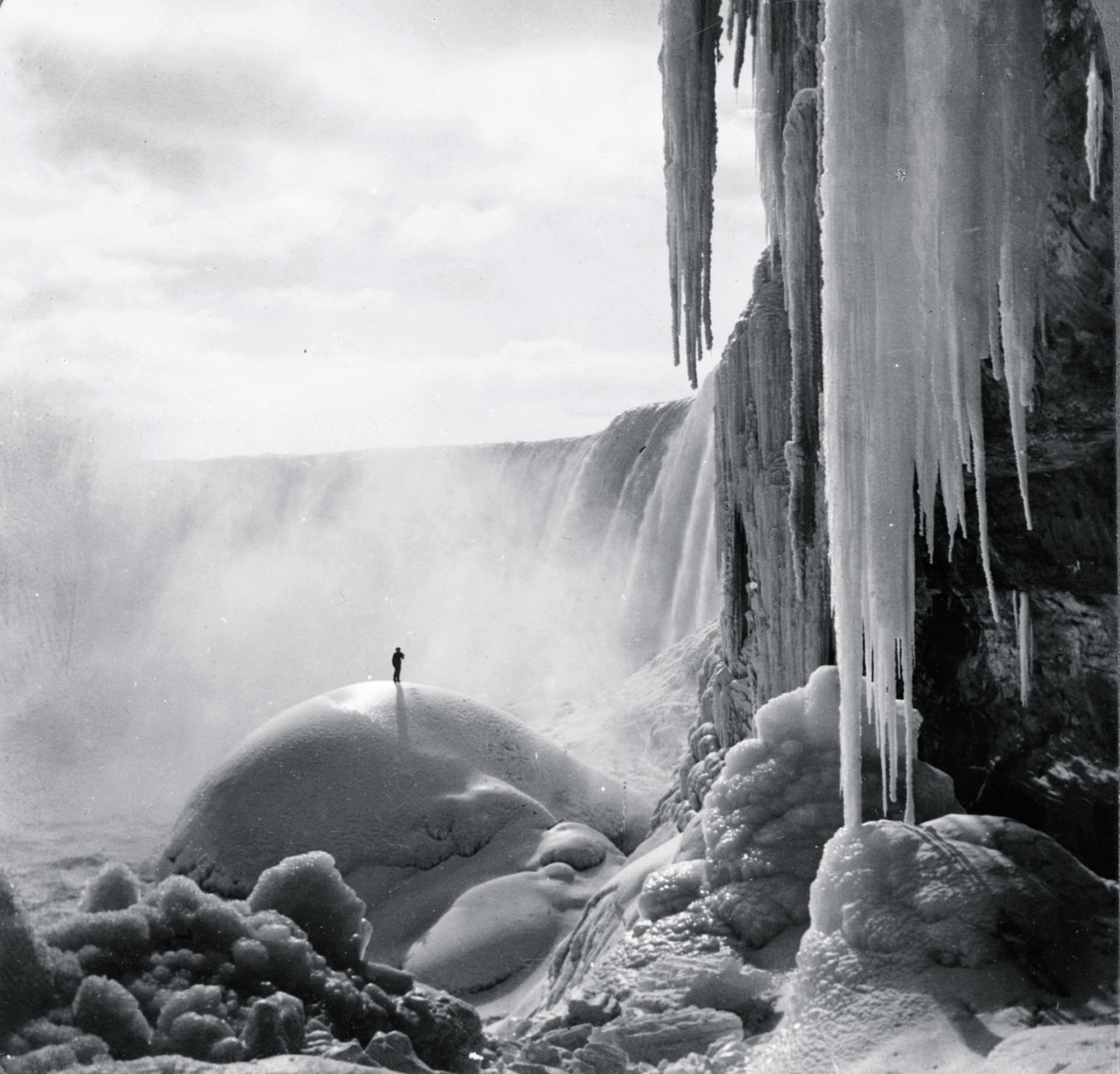 A lone wanderer stands at the foot of the partially frozen Niagara Falls © Getty