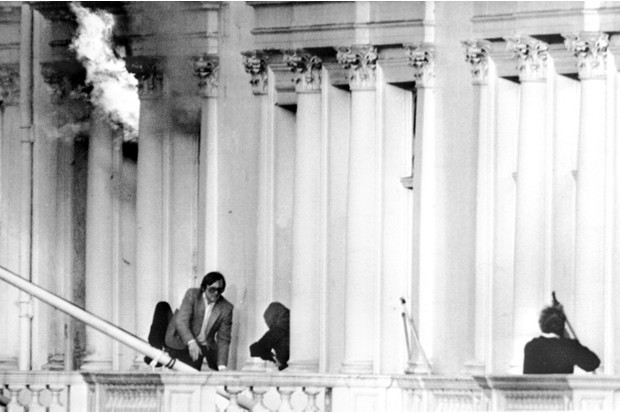 Hostage Sim Harris is the first out as he clambers over the balcony to safety, as a fire breaks out in the embassy © Getty Images