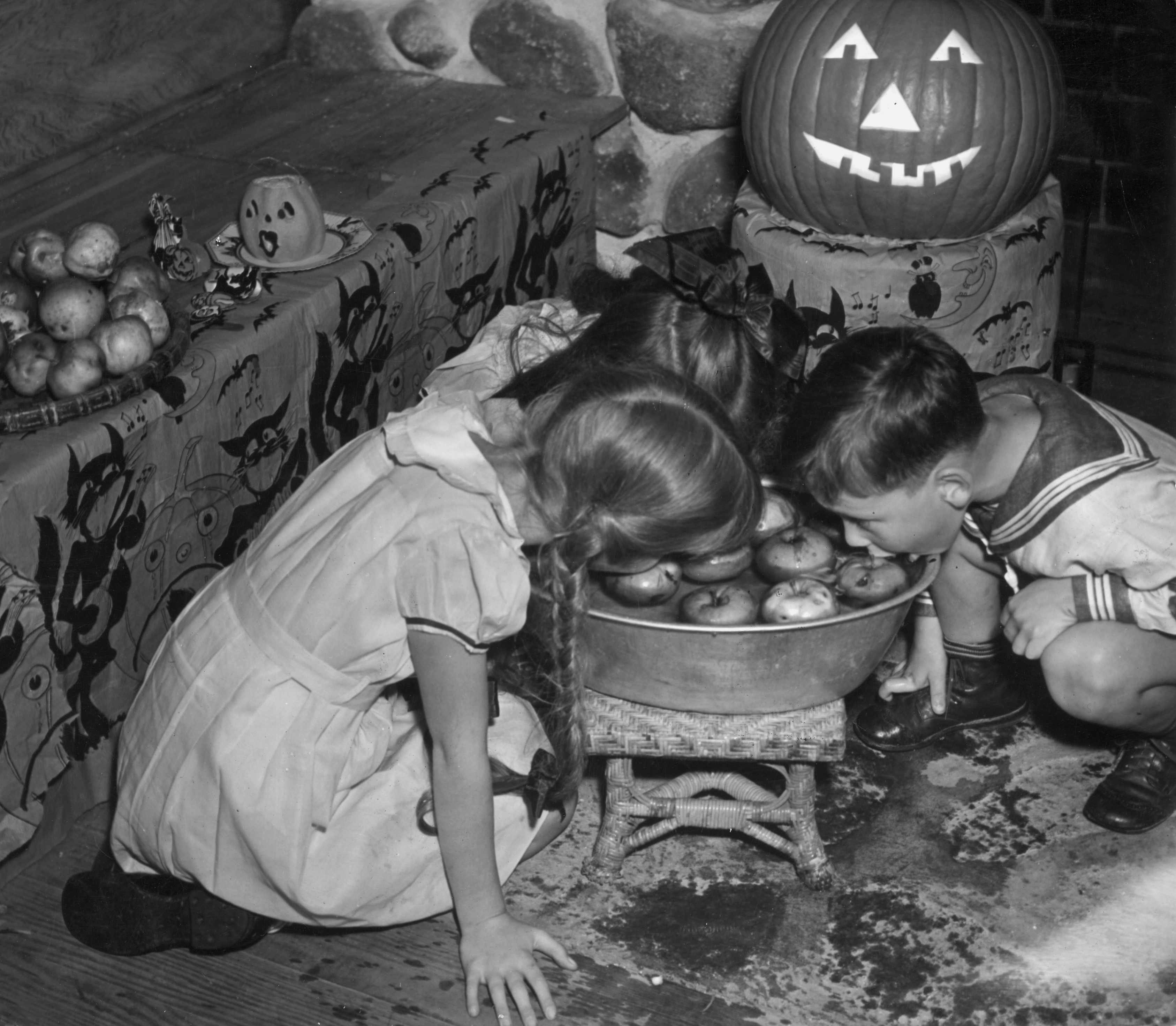 Children apple bobbing for Halloween, with an illuminated Jack-O-Lantern behind © Getty Images