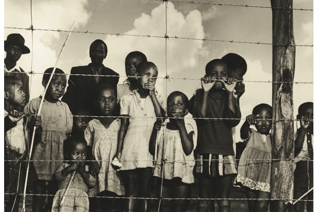 A group of children (and a few men) gaze from behind a barbed-wire fence that marks the boundary of the Moroka township in Soweta, Johannesburg in 1950 © Getty Images