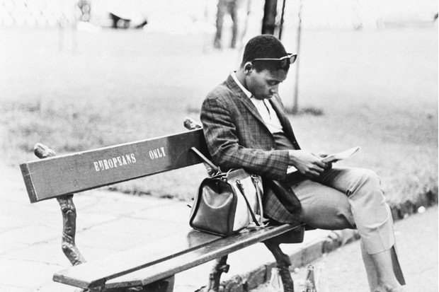 """Man Sitting on """"Europeans Only"""" Bench during Apartheid © Getty Images"""