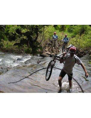 Riders sometimes need to carry their bikes across streams.