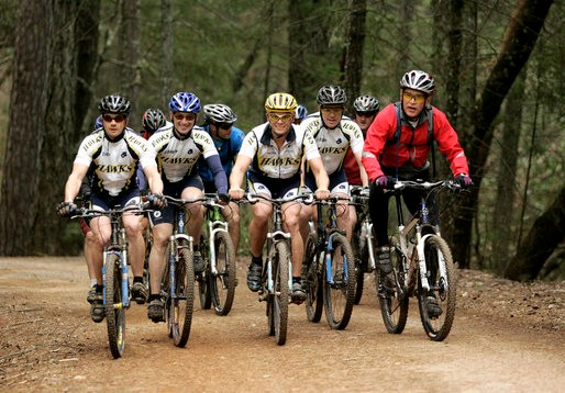 US President George Bush (R) rides with the Travis Air Force Base cycling team in 2006.
