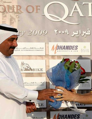 Britain's Roger Hammond (R), wearing the gold leader's jersey, accepts a bouquet of flowers from Qatar Cycling Federation President Khaled bin Ali al-Thani (L).