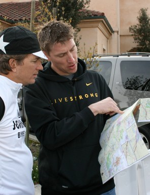 General manager Bart Knaggs (L) consults the day's planned route with team director Axel Merckx.