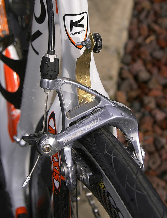 A simple number holder	is sandwiched in between the Red rear brake calliper and the frame.
