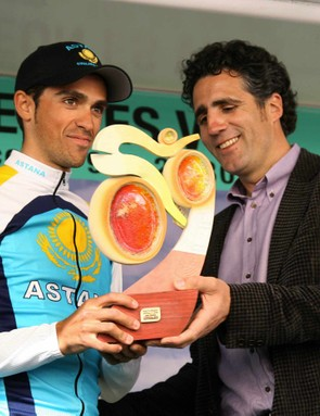 pain's Alberto Contador (L) of Astana smiles as five-time Tour de France winner and compatriot Miguel Indurain hands him a trophy after Stage 2 of the Castilla y Leon in Palencia, Spain on March 24, 2009.