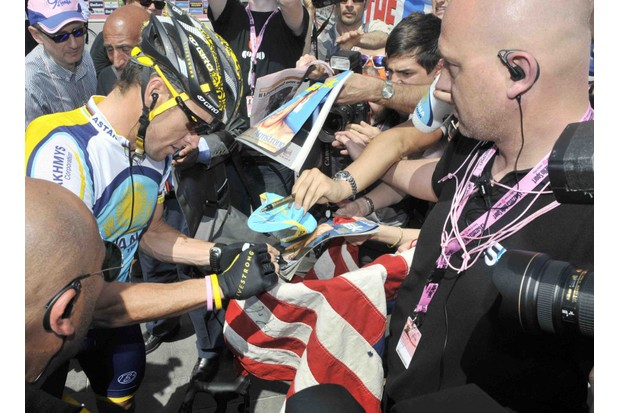 Lance Armstrong signs autographs before Stage 2 of the 2009 Giro d'Italia.