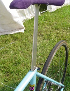 The hand crafted seatpost is topped by a purple velvety saddle