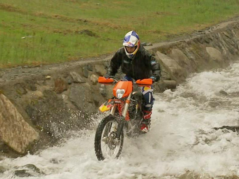 Gee riding a motocross bike up a waterfall