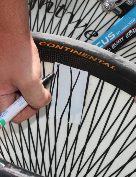 A team mechanic seals the valve access hole with white tape, then draws in the spokes with a marker. Not a shabby job, either, considering he was doing the work freehand and with an upside-down view