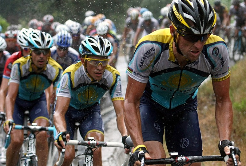 Lance Armstrong and Alberto Contador negotiate the dangerously wet sixth stage