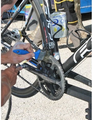 Solvent is poured into a cut-off water bottle, which is conveniently placed in the seat tube-mounted cage. A simple paint brush is used to apply the solvent to the drivetrain.