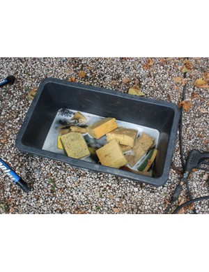 Tools of the trade: a tub full of soapy sponges and brushes, a pressure washer, and the legs of a Euro-style repair stand.