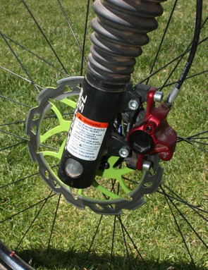 The front brake caliper clamps down on a lightweight metal matrix rotor from Scrub Components