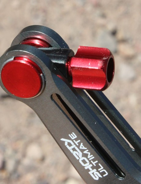 A barrel adjuster is integrated into the end of one arm.