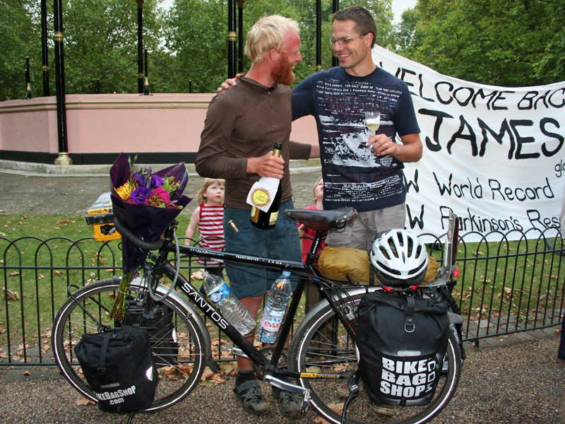 James Bowthorpe has a drink of champagne with Robbert Rutgrink, the MD of Santos, who supplied James with a bike