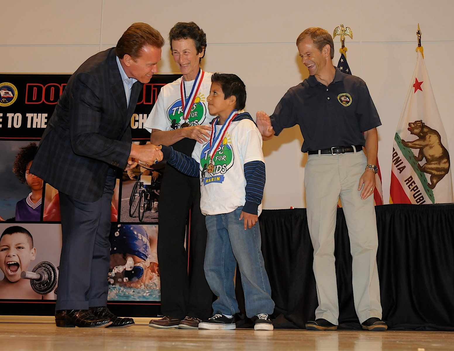 California governor Arnold Arnold Schwarzenegger presents award to Trips for Kids founder Marilyn Price and a student.