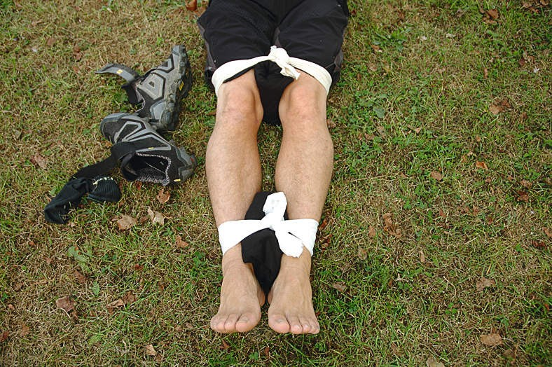 Carefully strap the legs together, being sure not to tie the bandages over the injury site or the knees. The idea is to keep the injured leg immobilised, by securing it to the uninjured one
