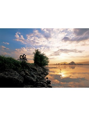 Cyclists rest on the shores of the River Aare, near Grenchen, Kanton Solothurn, on the Aare Route cycle trail
