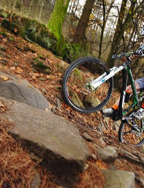 Billy keeps his weight on the rear to increase grip and hops the bike over the rocks