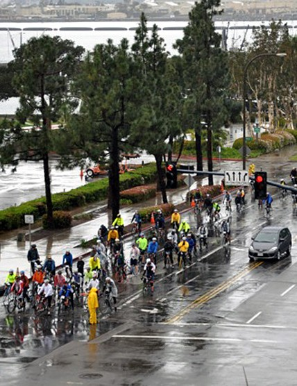 A group waits to proceed on San Diego's rain soaked streets