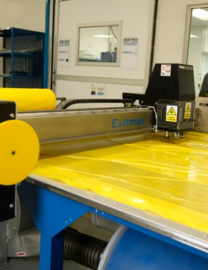 A vacuum pulls raw material down tightly against the surface of this table, where pieces are carefully cut using a computer-controlled blade
