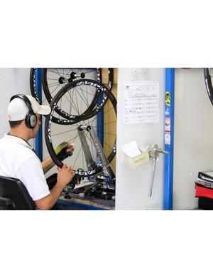 No, this worker isn't listening to tunes while building wheels - he's listening to the tone of each spoke as a measure of how even the tension is throughout the wheel