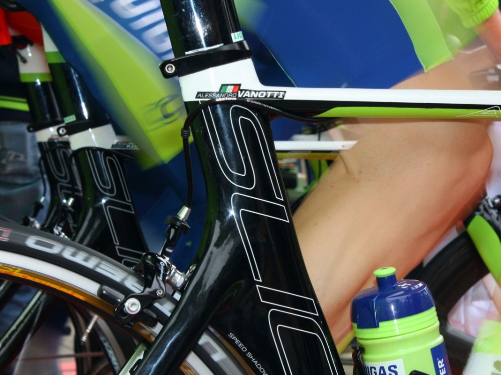 The rear brake housing is fed over and around the seat tube, presumably to tuck it in tighter against the frame