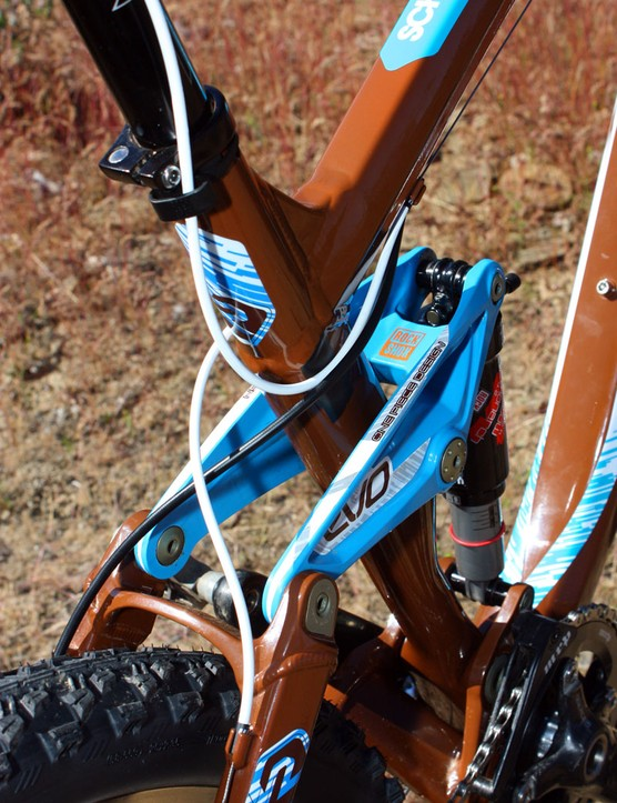 Housings are crossed behind the seat tube to keep them out of the way as the suspension compresses. The unused front derailleur housing stops are used for the seatpost remote